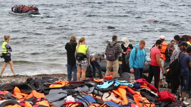 an overloaded boat of syrian migrants approaching the beach from turkey on the greek island of lesvos. - isil konflikt stock-videos und b-roll-filmmaterial