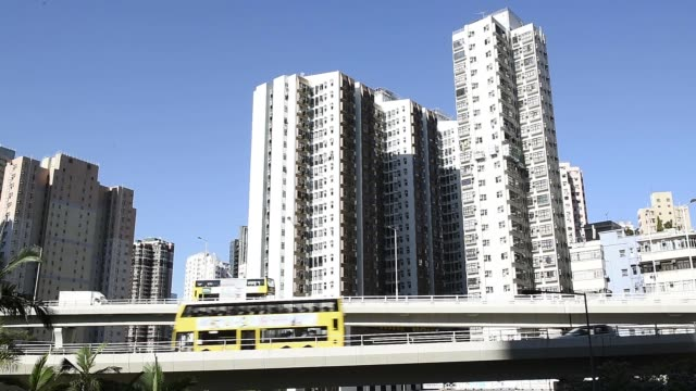 vídeos de stock e filmes b-roll de an overpass stands above the shau kei wan bus terminus next to residential buildings in the shau kei wan district of hong kong, china, on friday,... - sampana
