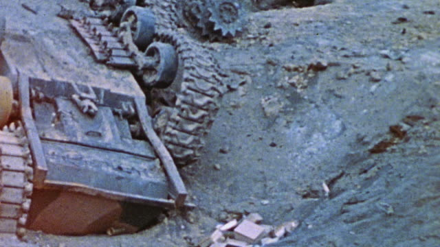 an overturned tank lays in the dirt with a burnt corpse partially crushed underneath it / iwo jima japan - schlacht um iwojima stock-videos und b-roll-filmmaterial