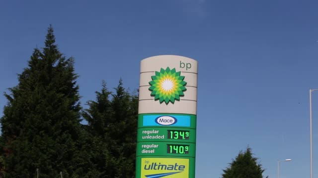 stockvideo's en b-roll-footage met an price sign stands at the entrance to a bp gas station operated by bp plc in london zoom in to bp logo pull out from bp logo on a price sign which... - bp