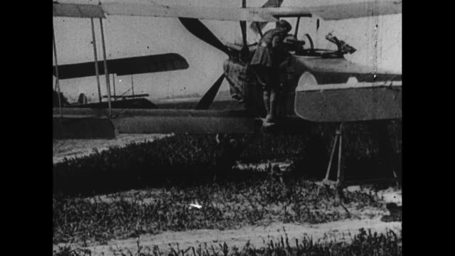an raf biplane is pushed from a hangar / a pilot checks his automatic guns atop an airplane / cheerful pilots joshing around / men in a muddy field... - 飛行機格納庫点の映像素材/bロール