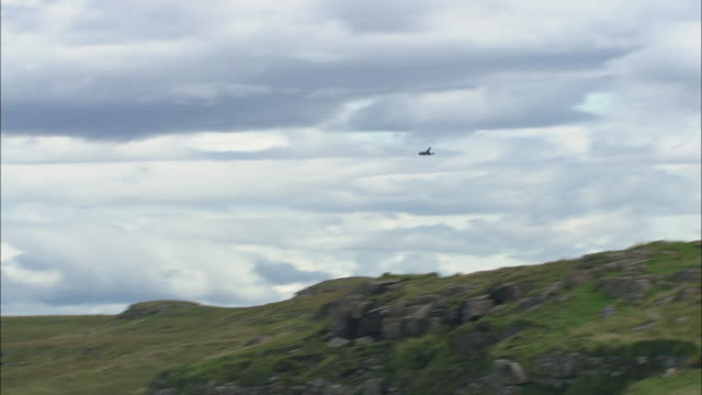 an raf fighter jet flies over the island of canna in the scottish inner hebrides.  - raf stock videos and b-roll footage