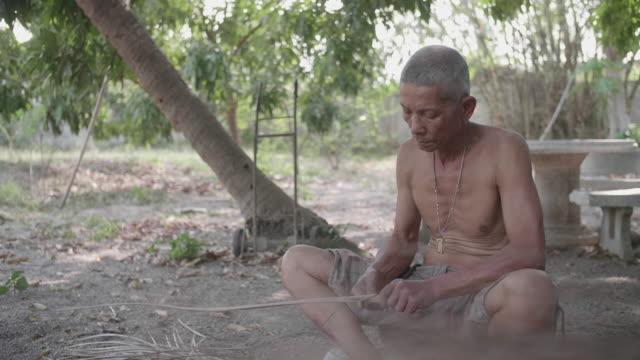 stockvideo's en b-roll-footage met een senior man maken een bezem met de hand tijdens de zomer. - alleen één seniore man