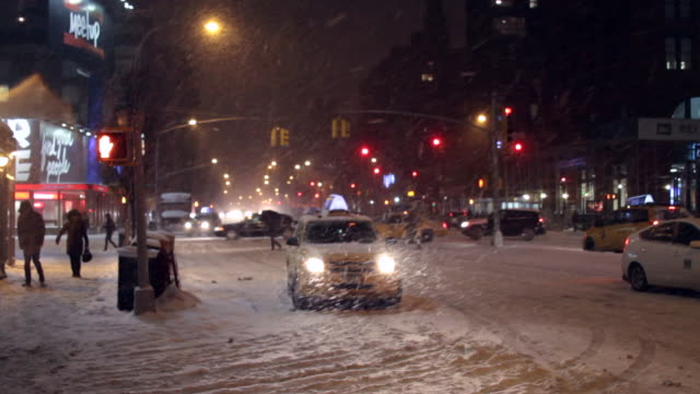 an snowy blizzard new york city traffic scene with people walking at night. - ladenschild stock-videos und b-roll-filmmaterial