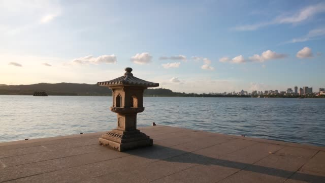 an stone lantern against downtown skyline by the west lake,hangzhou,china - lakeshore stock videos & royalty-free footage