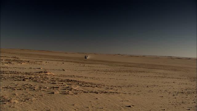 vídeos de stock, filmes e b-roll de an suv caravan drives across a barren area in the sahara desert. - comboio