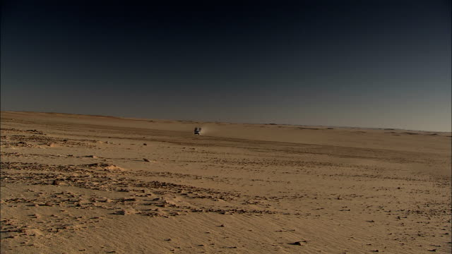 an suv caravan drives across a barren area in the sahara desert. - convoy stock videos & royalty-free footage