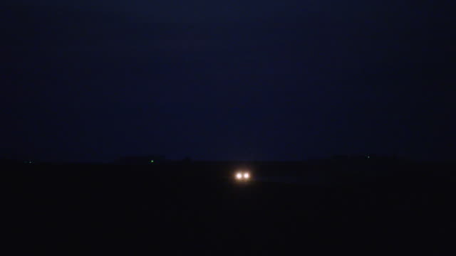 An SUV drives past camera on a rural country road with headlights and taillights glowing in the night.