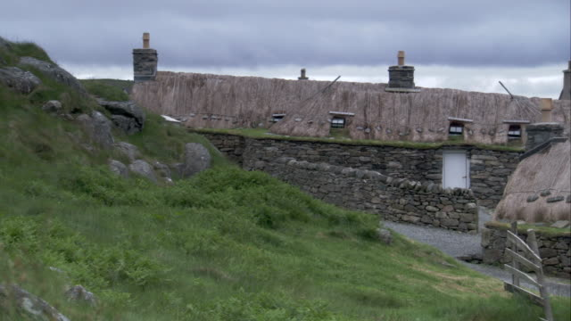 An SUV drives past the black houses of Gearrannan Scotland. Available in HD.