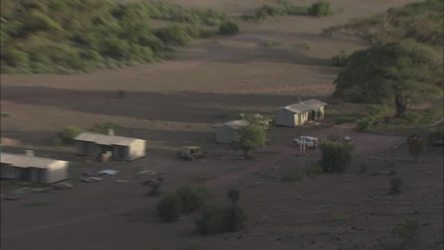 vídeos de stock e filmes b-roll de an suv pulls into a tiny village in kenya. - vegetação de pasto