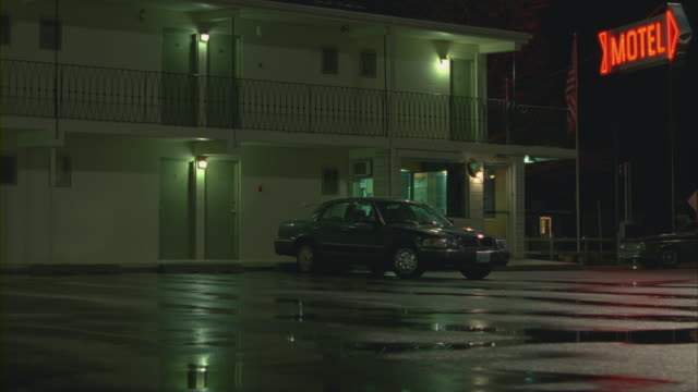 an suv pulls into the parking lot of a motel on a rainy night. - motel stock videos and b-roll footage