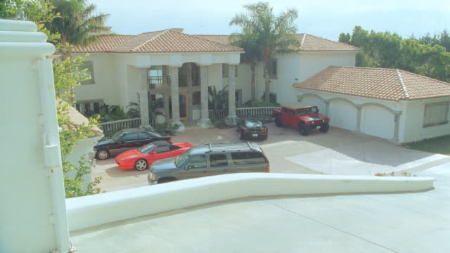 an suv pulls up to a mansion and parks in front of a three car garage. - zweistöckiges wohnhaus stock-videos und b-roll-filmmaterial