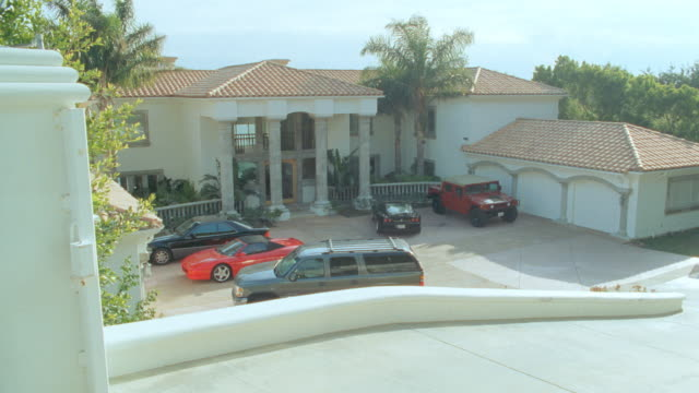 an suv pulls up to a mansion and parks in front of a three car garage. - driveway stock videos & royalty-free footage