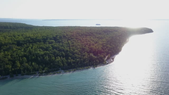 an sweeping drone view of the bike lane, trees and a small cruise ship around mackinac island - michigan stock videos & royalty-free footage