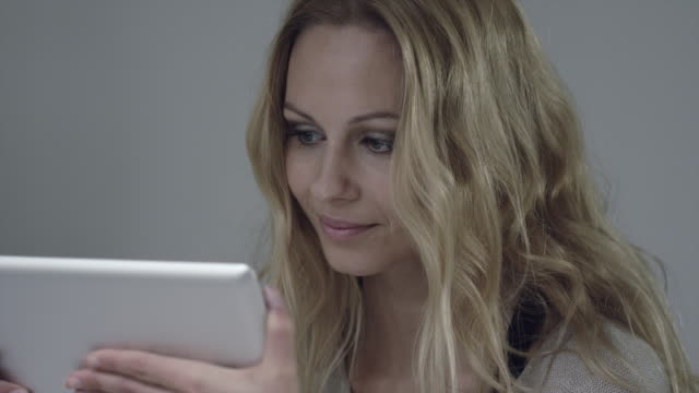 An iPad screen illuminates the face of a young woman as she holds and looks at it.