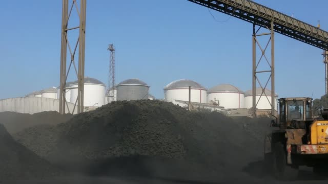 an truck drives past mounds of coal as fuel storage tanks stand beyond at the vttv oil storage terminal a joint venture of vitol group and misc bhd... - sifting stock videos and b-roll footage