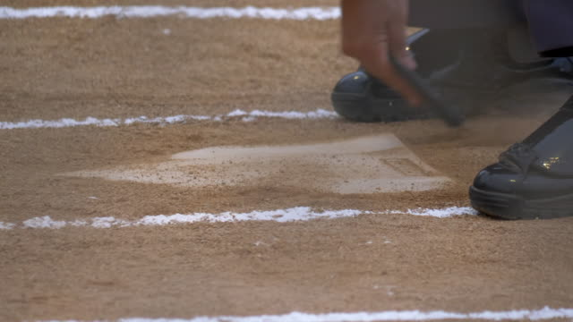 an umpire at a little league baseball game brushing off home plate base. - slow motion - brushing stock videos & royalty-free footage