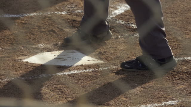 vídeos y material grabado en eventos de stock de an umpire brushes off home plate at a little league baseball game. - quitar el polvo