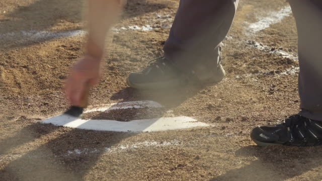 An umpire brushes off home plate at a little league baseball game.