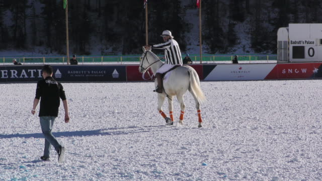 An umpire collects a horseshoe lost during a polo match at the Winter Polo World Cup on January 29 2016 in St Moritz NO