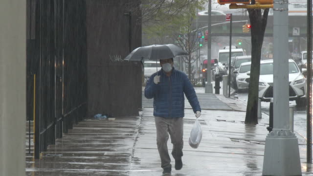 an unidentified man carrying an umbrella and wearing a surgical mask and protective vinyl gloves walks down junction boulevard during a heavy rain... - scott mcpartland stock videos & royalty-free footage