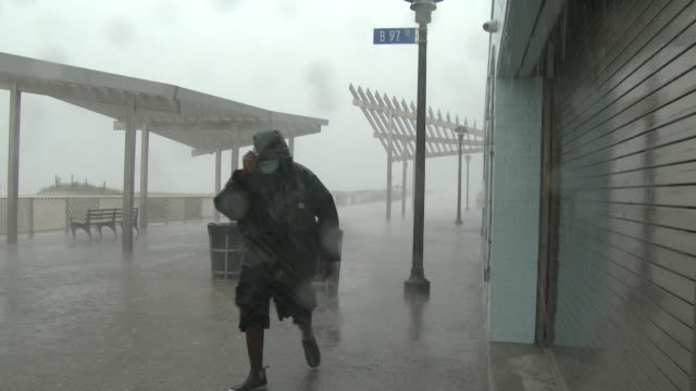 an unidentified man wearing a mask shields his face from wind driven torrential rain on rockaway beach during tropical storm isaias queens new york... - scott mcpartland stock videos & royalty-free footage