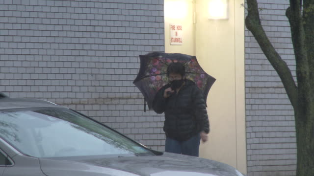 an unidentified person wearing a protective face mask walks in the rain with an umbrella in hand on junction boulevard in the elmhurst neighborhood... - scott mcpartland stock videos & royalty-free footage
