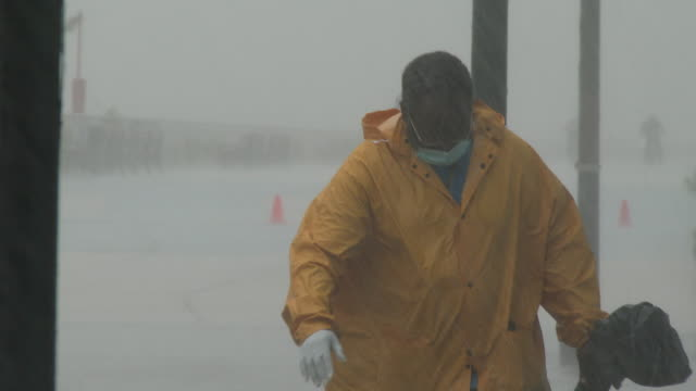 an unidentified sanitation worker wearing a mask and gloves collects trash on the boardwalk as torrential rain falls during tropical storm isaias on... - scott mcpartland stock videos & royalty-free footage