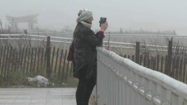 an unidentified woman takes pictures with her cell phone on rockaway beach during an early spring coastal storm queens new york new york - scott mcpartland stock videos & royalty-free footage