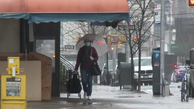 an unidentified woman wearing a surgical mask and vinyl gloves pulls a shopping cart in one hand while carrying an umbrella in the other as rain... - scott mcpartland stock videos & royalty-free footage