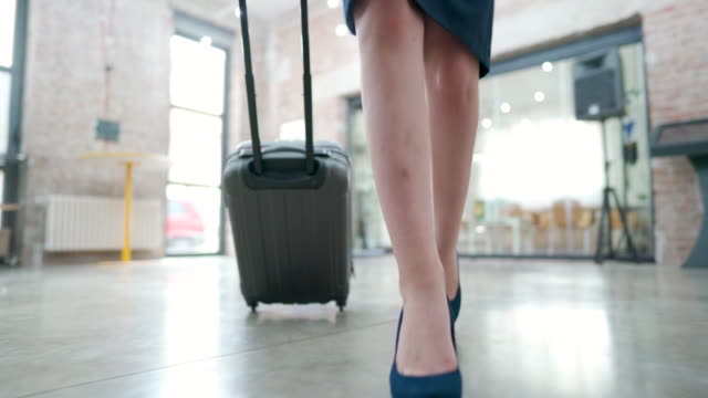 an unrecognizable female person coming in and dragging a suitcase - reportage stock videos & royalty-free footage