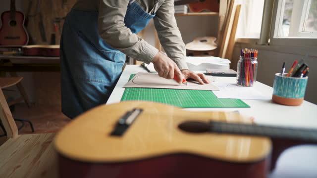 vídeos y material grabado en eventos de stock de un hombre irreconocible cortando la forma de una guitarra en papel, trabajando en un nuevo modelo en el taller - talla