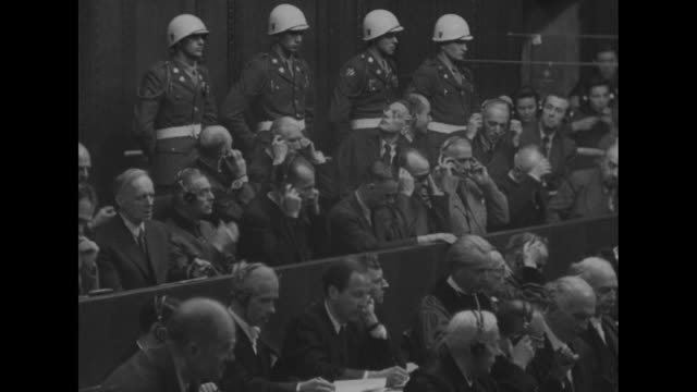 vs an unseen justice calls for adjournment and the defendants rise men talking amongst themselves franz von papen chats with others as whitehelmeted... - processi di norimberga video stock e b–roll