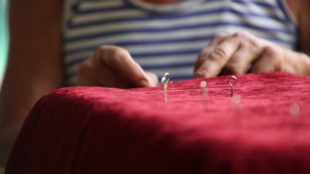 An upholsterer sews a seat cushion.