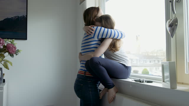 an upset girl sitting on window sill. her mother comes in and gives her a cuddle - single mother stock videos & royalty-free footage
