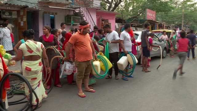 vidéos et rushes de an urban slum in indian capital city of delhi struggles for drinking water. three tankers bring water to this locality every day but the wait for... - limite