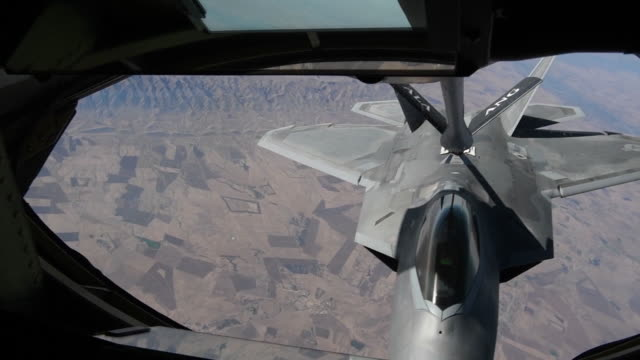 an us air force kc135 stratotanker refuels a f22 raptor over northern iraq - us airforce stock videos & royalty-free footage