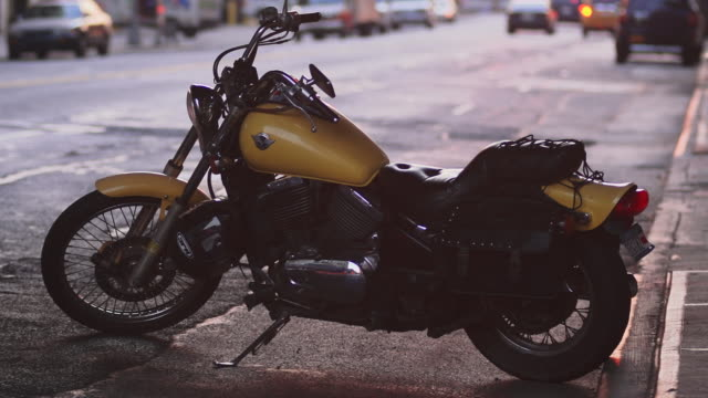 vídeos de stock e filmes b-roll de an vintage motorcycle sits by the curb in new york - parado
