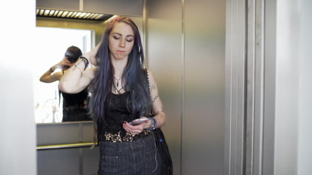 vídeos de stock, filmes e b-roll de an young woman with purple hair in an elevator - estilo de vida alternativo