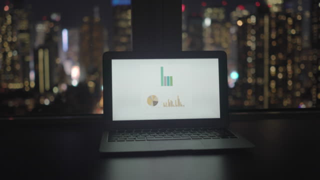 analyzing business growth charts on laptop computer screen in modern city office - entusiasta di tecnologia video stock e b–roll