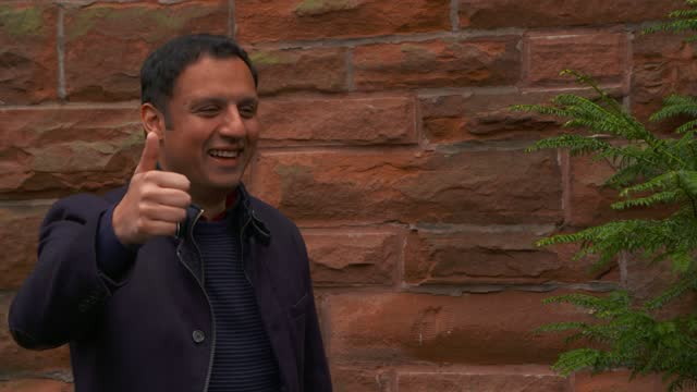anas sarwar - leader of the scottish labour party - gives a thumbs up and blows a kiss to photographers as he arrives at a polling station with his... - correspondence stock videos & royalty-free footage