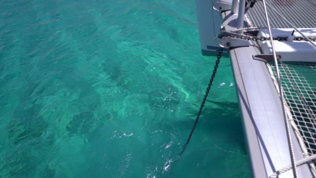 vídeos de stock e filmes b-roll de anchor drops to ocean bottom from sailboat - ancora