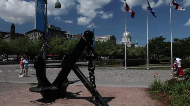 MS TU Anchor, quebec and canadian flag and tourists walking at old port / Montreal, Quebec, Canada