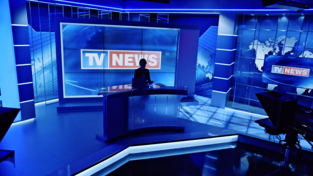 cs anchor woman standing at the desk in the studio as the lights go on and she starts the evening news - news event stock videos & royalty-free footage