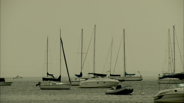 anchored boats bob on a quiet sea. available in hd. - anchored stock videos & royalty-free footage