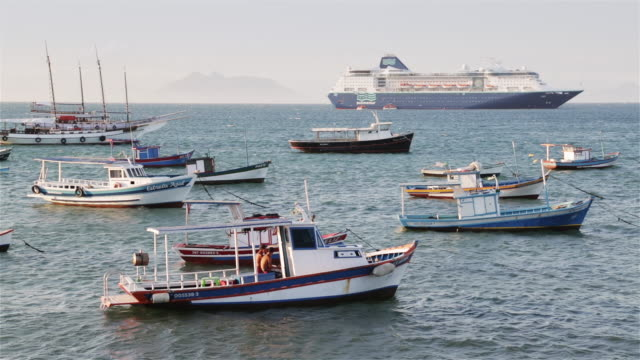 vídeos de stock, filmes e b-roll de ls anchored fishing boats and a cruise liner / buzios, brazil - cruzeiro
