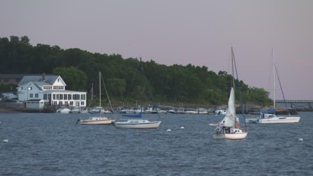 Anchored mid size sail boats floating near a marina