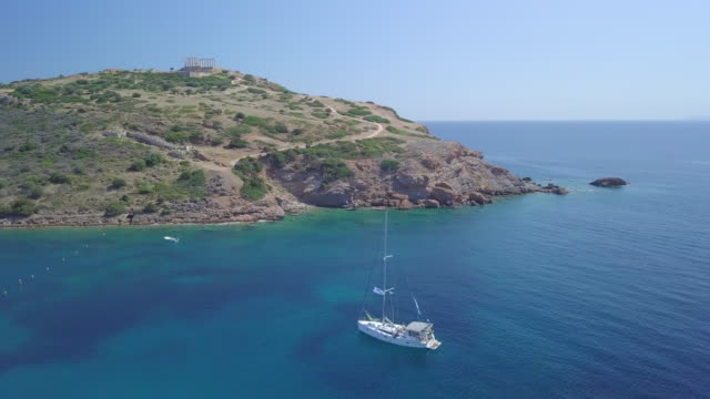 anchored sailboat aerial drone view near temple of poseidon, sounion, greece. - anchored stock-videos und b-roll-filmmaterial