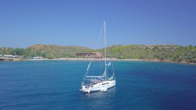 anchored sailboat aerial drone view near temple of poseidon, sounion, greece. - anchored stock videos & royalty-free footage