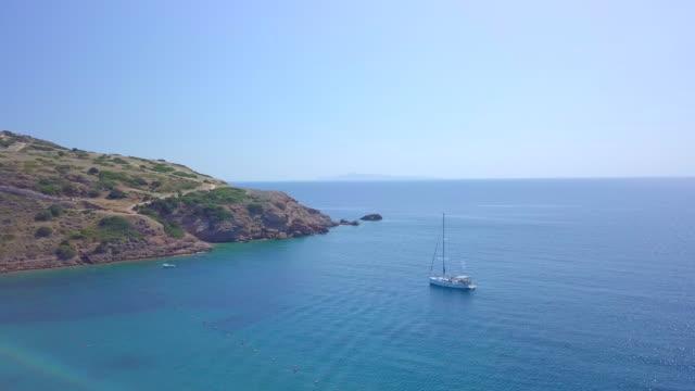 vídeos y material grabado en eventos de stock de anchored sailboat aerial drone view near temple of poseidon, sounion, greece. - grecia europa del sur